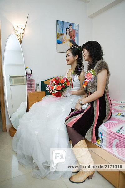 Braut sitzt mit Freund auf dem Bett  schaut weg  lächelt  volle Länge