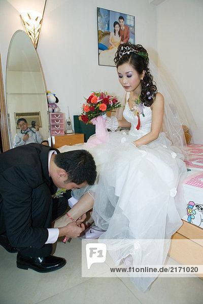 Bräutigam setzt Schuh auf Brautfuß im Schlafzimmer