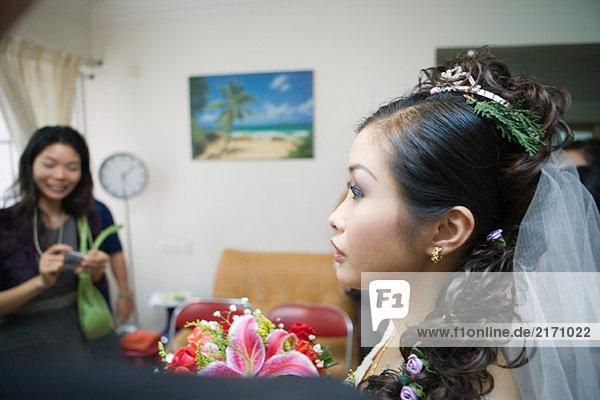 Braut mit Schleier  immergrüner Zweig im Haar  im Wohnbereich  Profil