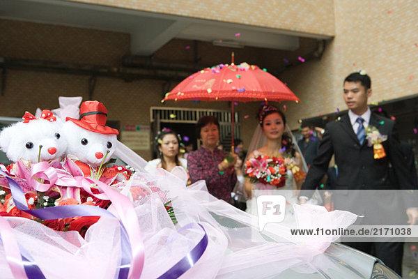 Chinesische Hochzeit  Braut und Bräutigam verlassen unter Konfetti  Braut mit rotem Sonnenschirm bedeckt  dekoriertes Auto im Vordergrund