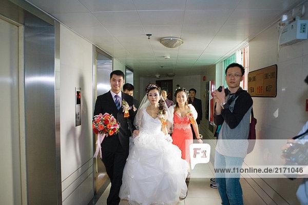 Braut und Bräutigam gehen durch den Flur und Fotografen stehen mit Kameras bereit.