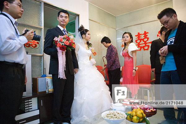 Chinesische Hochzeit  Brautpaar stehend  Essen und Trinken auf dem Tisch