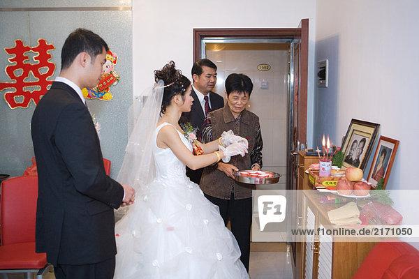 Chinesische Hochzeit  Braut nimmt Opfergabe an den Urheiligtum an