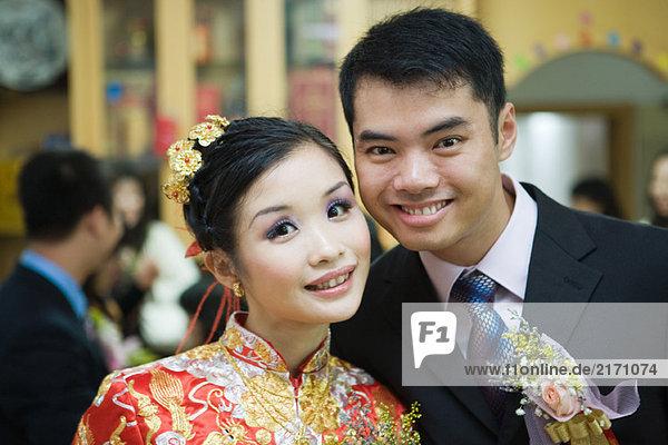 Neuvermählte lächeln vor der Kamera  Braut in traditioneller chinesischer Kleidung