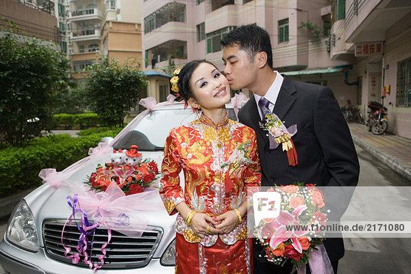 Bräutigam küssende Braut auf der Wange vor dem Auto