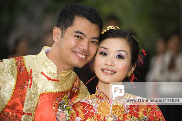 Braut und Bräutigam lächeln gemeinsam vor der Kamera  beide in traditioneller chinesischer Kleidung.