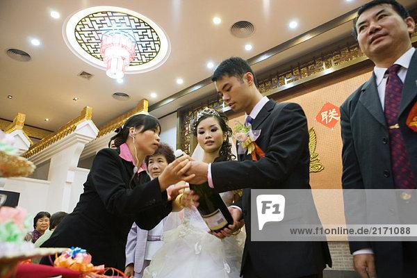 Frau hilft Braut und Bräutigam  Champagnerflasche öffnen  Blickwinkel niedrig
