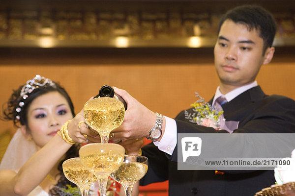 Braut und Bräutigam gießen Champagner in gestapelte Champagnergläser.