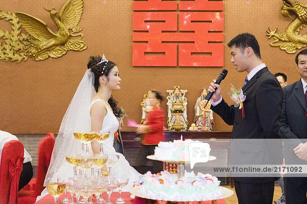 Braut und Bräutigam stehen von Angesicht zu Angesicht  schauen einander an  Bräutigam spricht ins Mikrofon