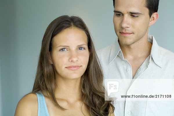 Teenage girl smiling at camera  young man standing behind and looking at her