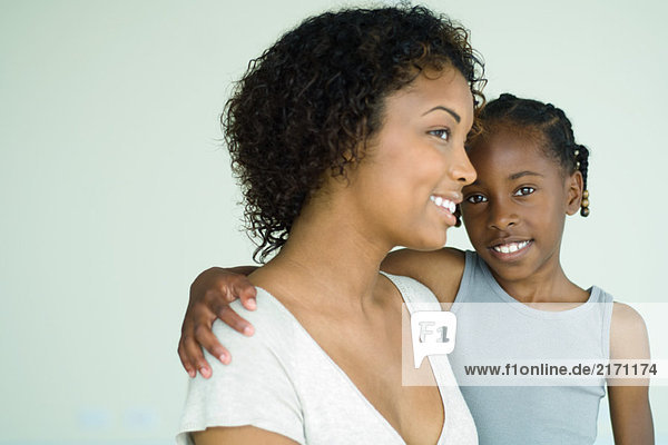 Mother holding daughter  both smiling  girl looking at camera