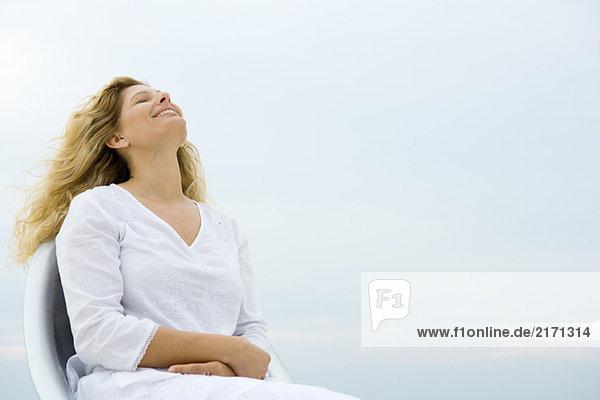 Frau sitzend mit geschlossenen Augen und Kopf zurück  lächelnd  Himmel im Hintergrund  Tiefblick
