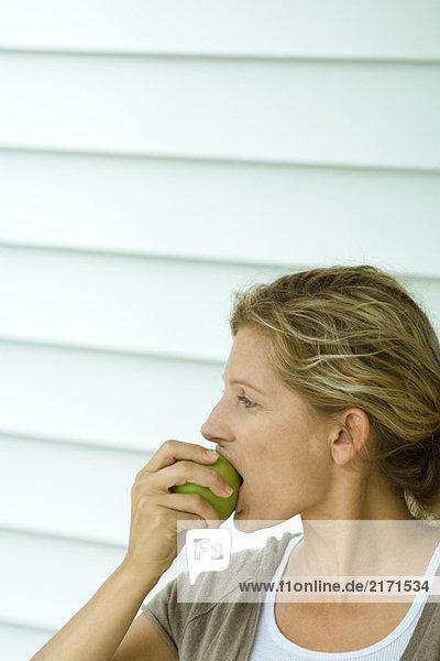 Frau beißt aus dem Apfel  Seitenansicht