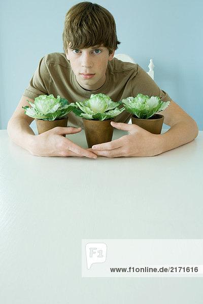 Teen boy holding arms around plants