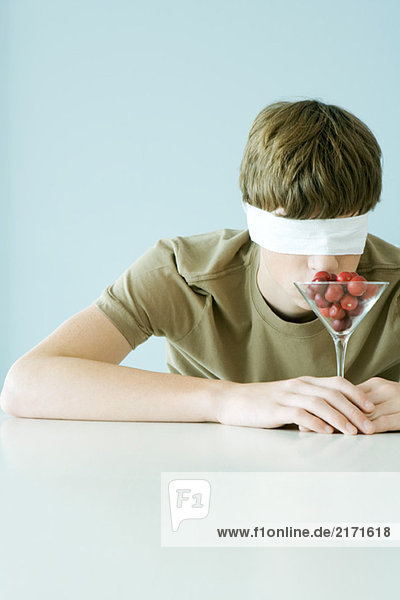 Young male wearing blindfold  smelling glass full of cherry tomatoes