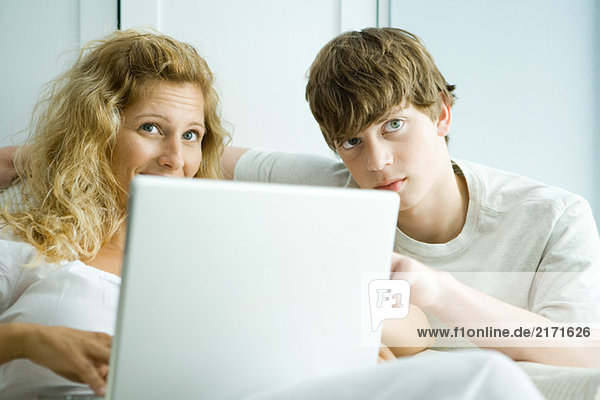 Woman and teen son using laptop  looking up
