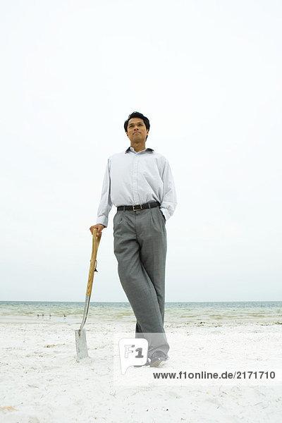 Mann steht am Strand  lehnt sich an Schaufel  Hand in Hand
