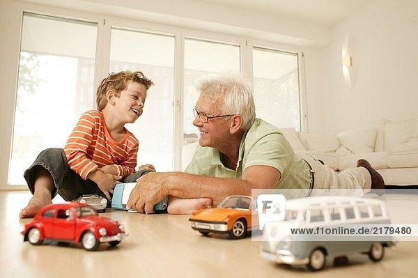 älterer Mann und sein Enkel spielen mit Auto