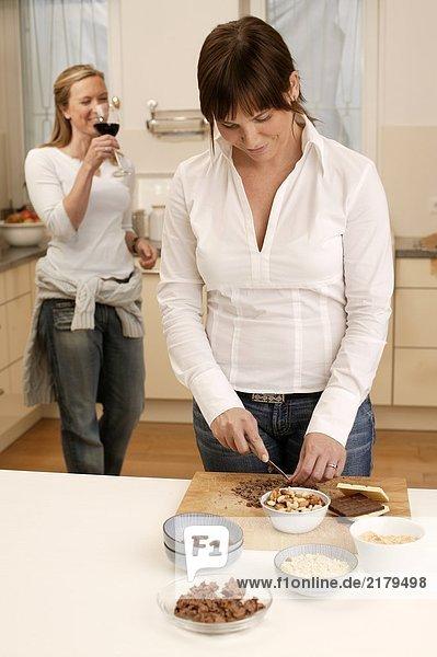 Frau Vorbereitung Essen in Küche und ihre Mutter im Hintergrund