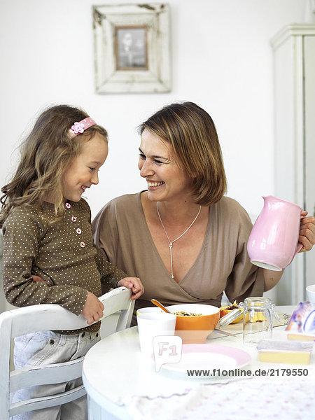 Mädchen und ihre Mutter lächelnd am Frühstückstisch