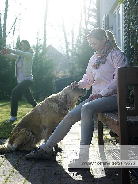 junge Frau junge Frauen üben Hund Hintergrund streicheln Freund