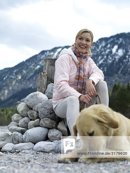 Junge Frau sitzend mit Hund am Flussufer