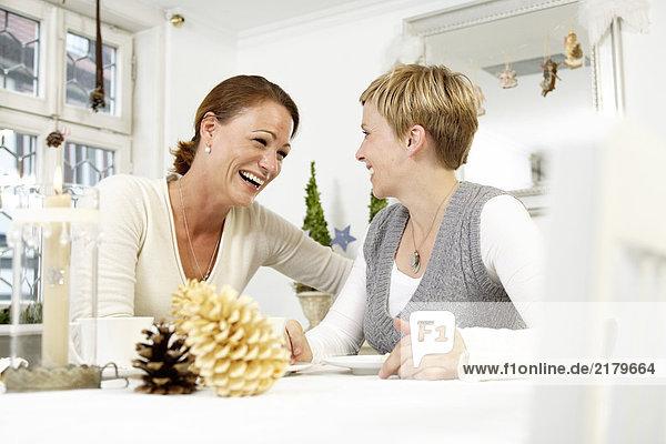 Zwei Frauen Lächeln am Tisch