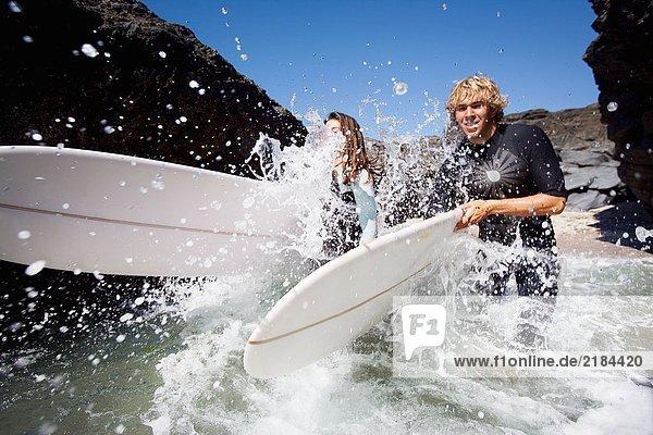 Ein Paar läuft im Wasser mit lächelnden Surfbrettern.