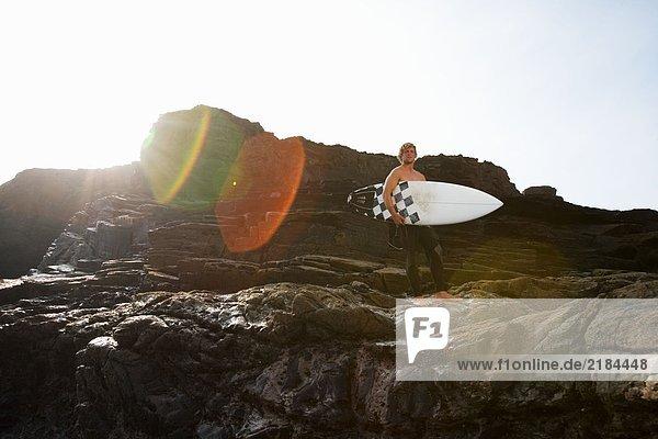 Mann hält Surfbrett auf großen Felsen.