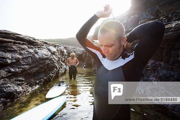 Zwei Männer im Wasser machen sich zum Surfen bereit.