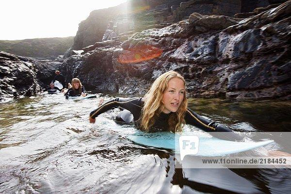 Vier Leute liegen auf Surfbrettern im Wasser und lächeln.