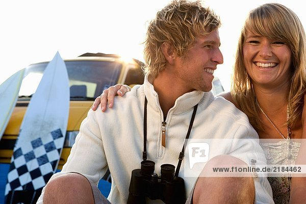 Ein Paar sitzt am Strand und lächelt mit Van und Surfbrettern im Hintergrund.