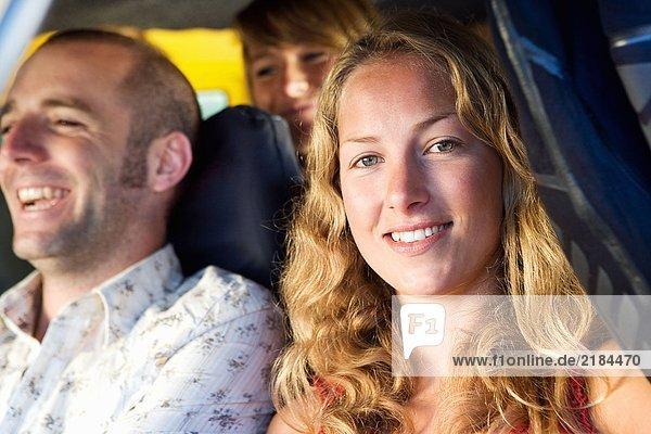 Drei Leute in einem Van lächeln.