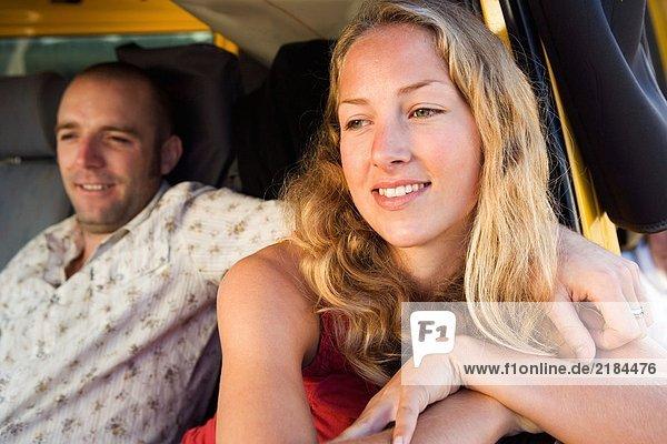 Ein Paar in einem Lieferwagen lächelnd.