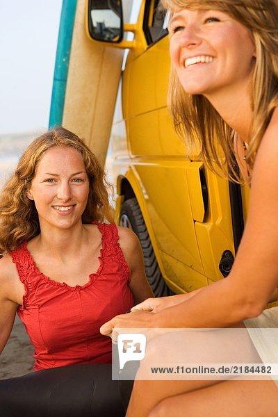 Zwei Frauen sitzen bei einem Van und lächeln mit Surfbrettern im Hintergrund.