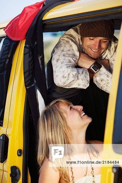 Ein Paar in einem Van  das sich anlächelt.