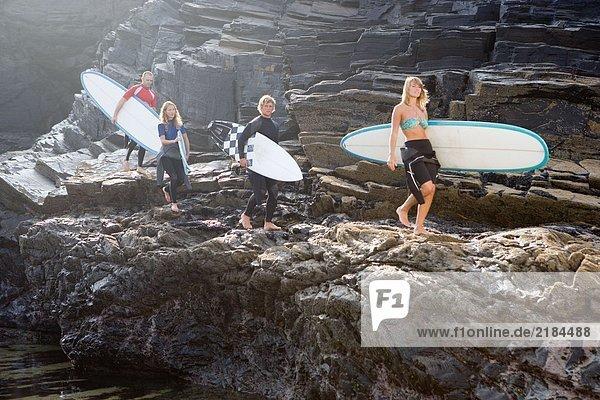 Vier Leute tragen Surfbretter auf großen Felsen.
