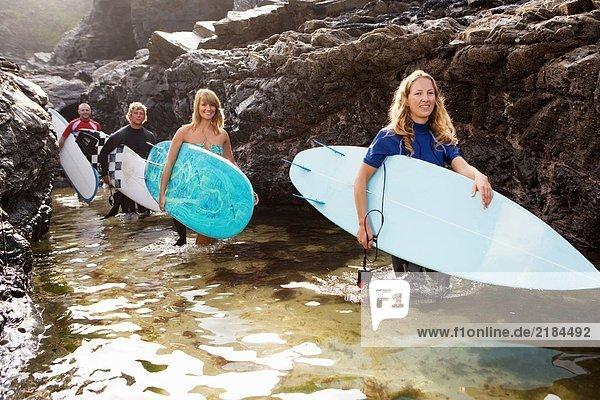 Vier Leute tragen Surfbretter an großen Felsen lächelnd.