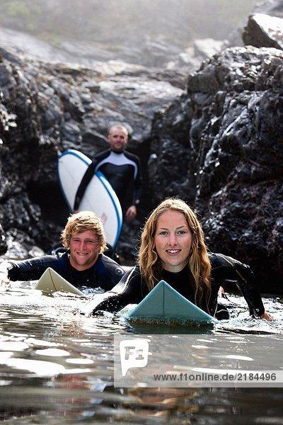 Drei Leute mit lächelnden Surfbrettern.