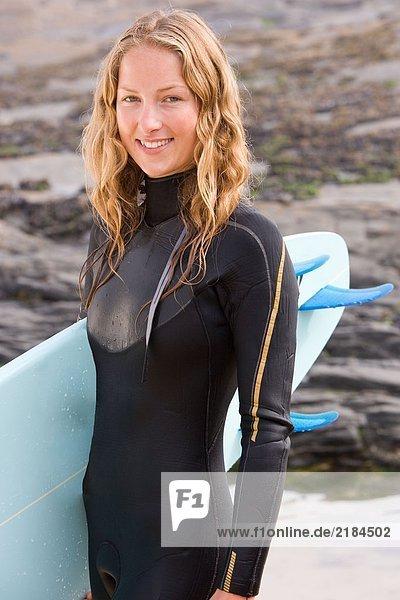 Frau stehend mit Surfbrett lächelnd .