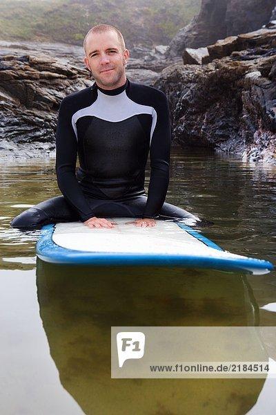 Mann sitzt auf dem Surfbrett im Wasser.
