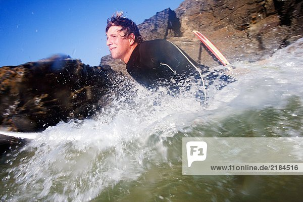 Mann auf dem Surfbrett im Spritzwasser.