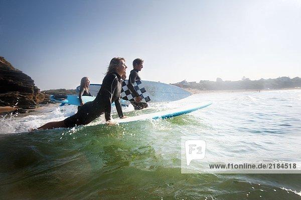 Vier Leute gehen lächelnd raus zum Surfen.