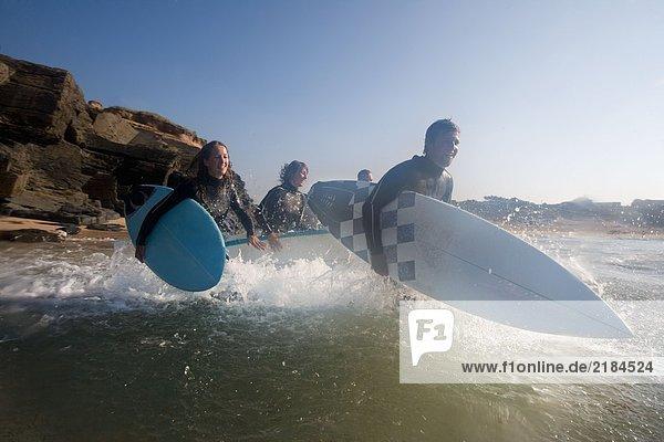 Vier Leute laufen mit lächelnden Surfbrettern ins Wasser.