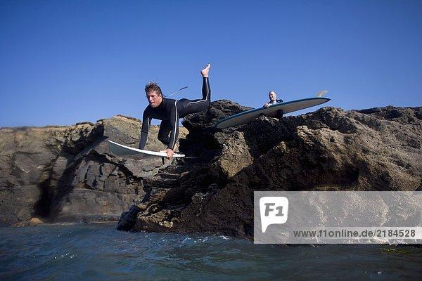Ein Mann springt auf das Surfbrett  während ein anderer Mann auf Steinen hinter ihm sitzt.