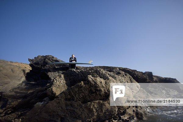 Mann sitzt mit Surfbrett auf großen Felsen und lächelt.