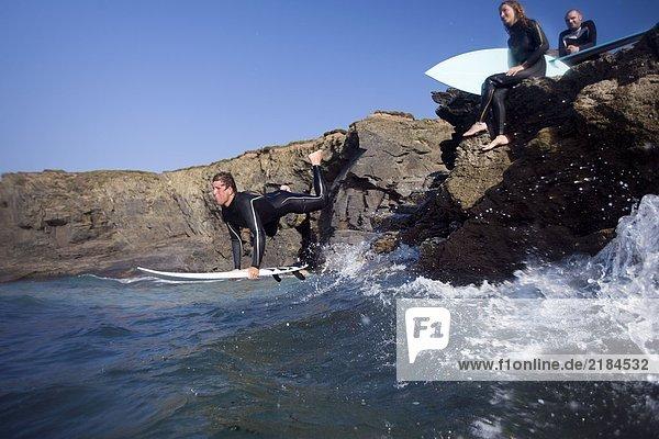 Mann  der auf dem Surfbrett ins Wasser springt und zwei Leute auf großen Felsen lächelnd sitzen.
