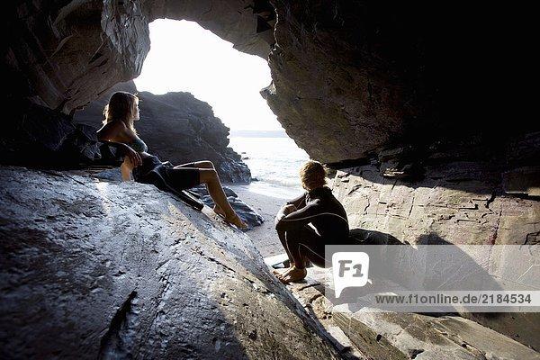 Ein Paar sitzt auf großen Felsen in Neoprenanzügen.