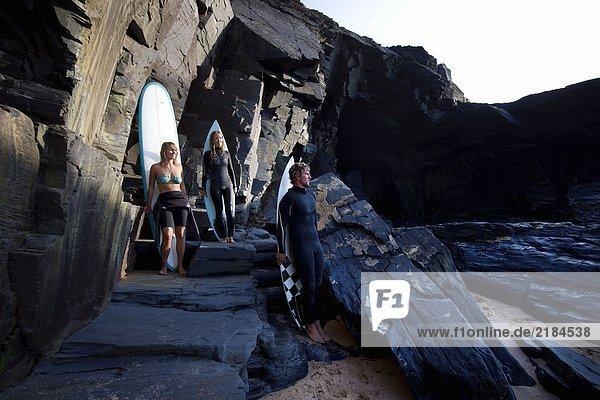 Drei Leute stehen mit Surfbrettern auf großen Felsen und lächeln.