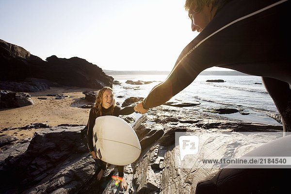 Mann hilft Frau mit Surfbrett auf großen Felsen lächelnd.